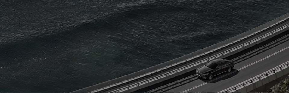 A car is driving on the bridge of sea.